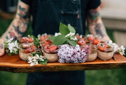 photo of chef holding tray of deserts with lilacs