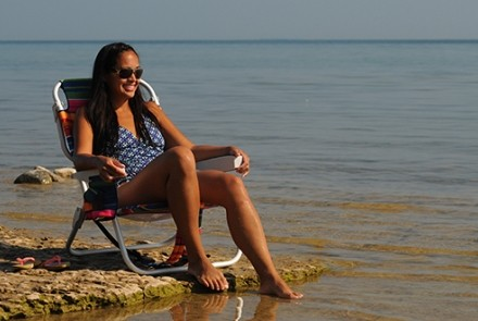 Woman sitting in a lawn chair on sand by the beach