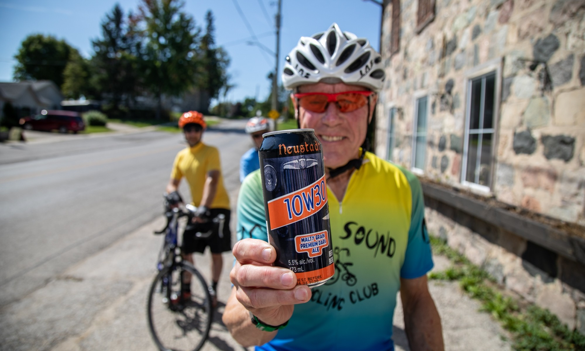 Man in cycling apparel holding beer can