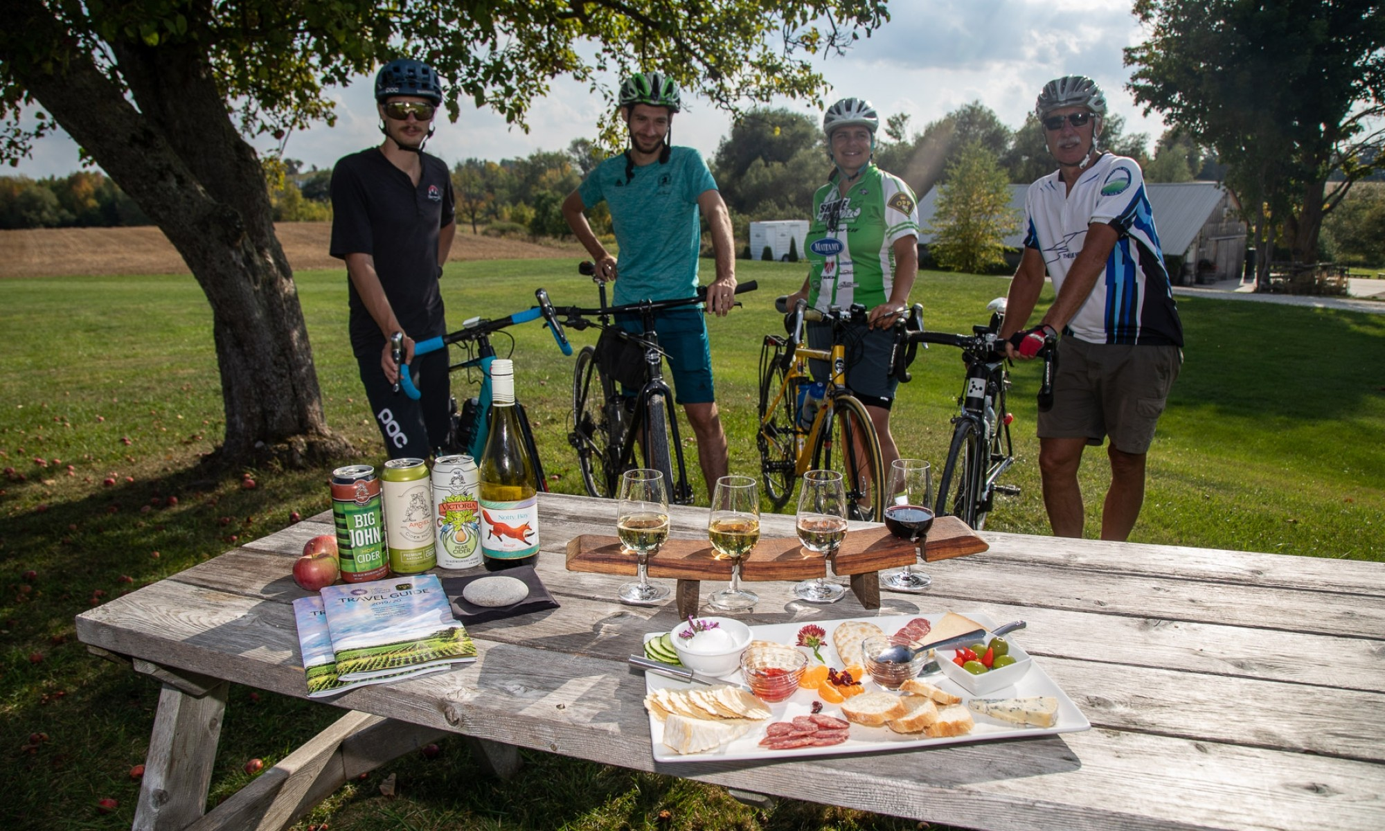 Four cyclists standing behind a charcuturie platter and flight of wine