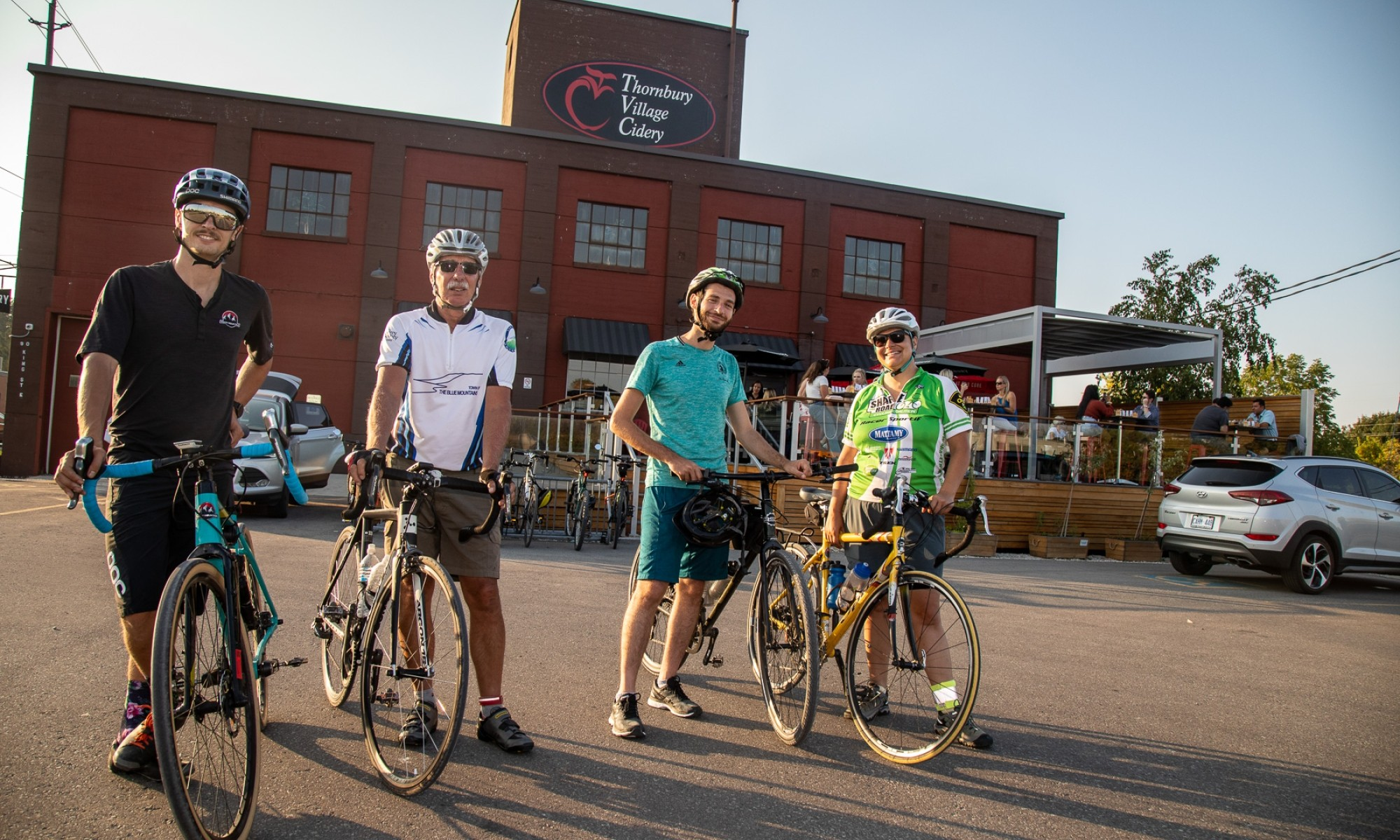 Four cyclists standing in front of Thornbury Cider House
