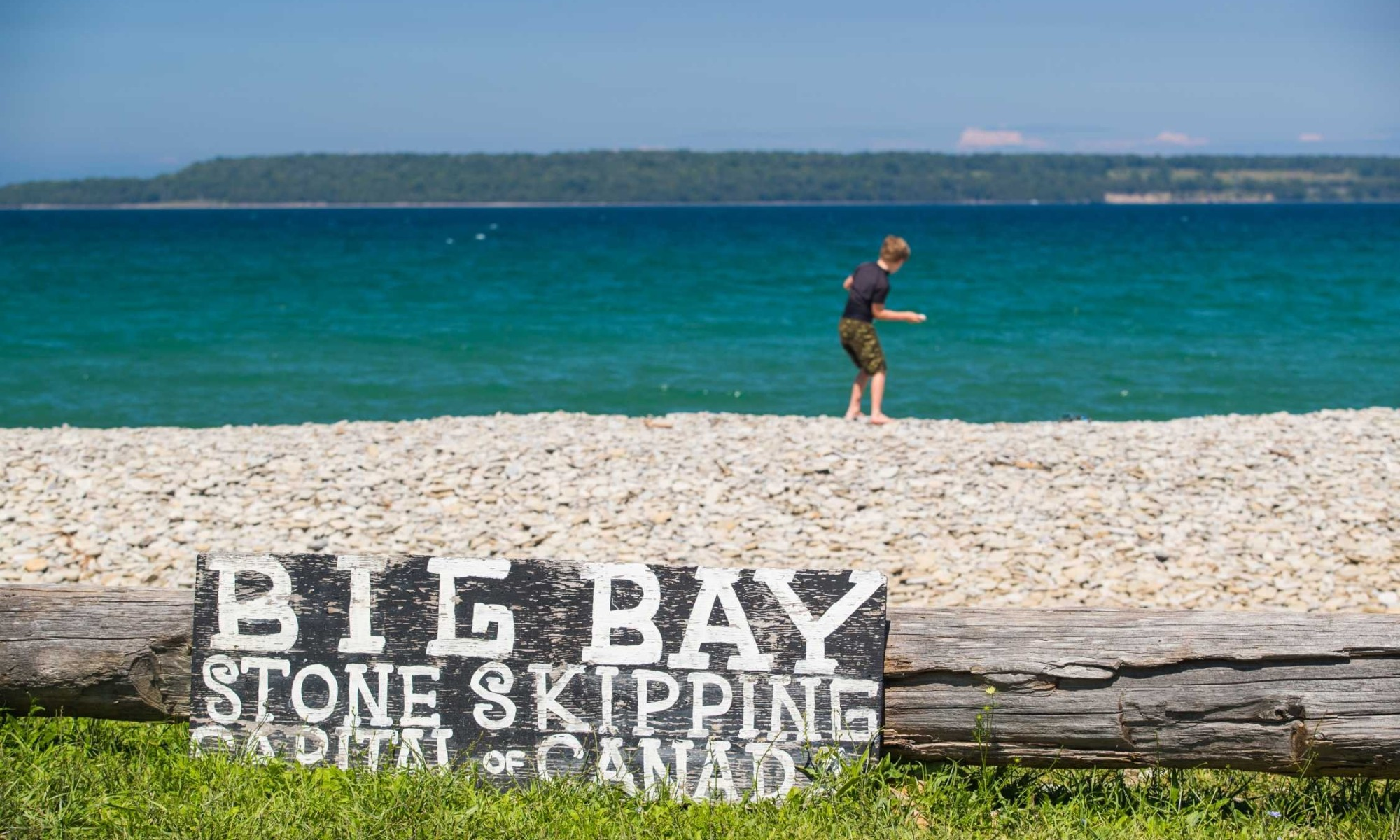Big Bay stone skipping sign with young boy skipping rocks