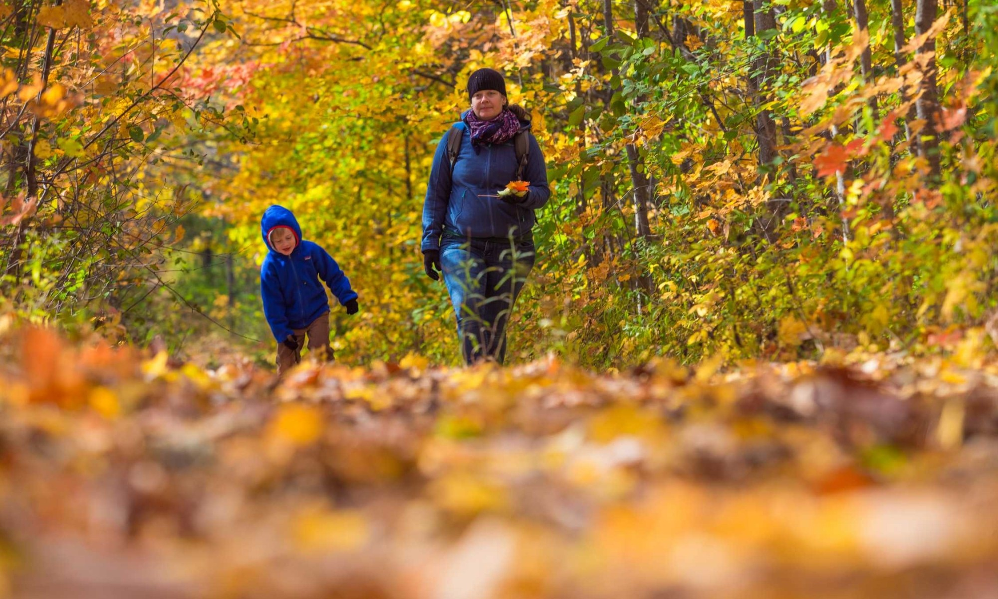 Rheanna and her son walking in the fall leaves